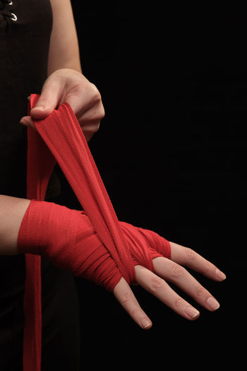 Close-up of woman hand holding red over black background