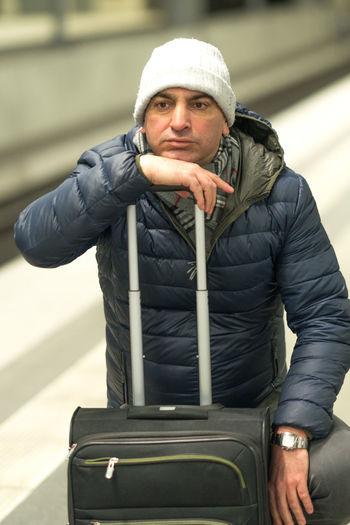 Man with luggage at railroad station platform
