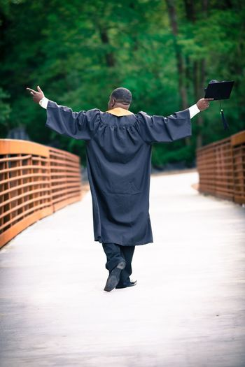 Male graduate in cap and gown with arms raised walking across bridge. Atlanta Beltline African-american African American Cap And Gown Graduate Walking Away Walking One Person Real People Men Lifestyles Full Length Rear View Human Arm Arms Outstretched Arms Raised Adult Outdoors