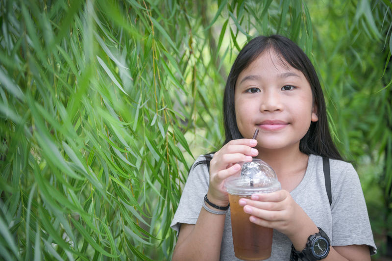 Portrait of smiling girl holding juice against plants