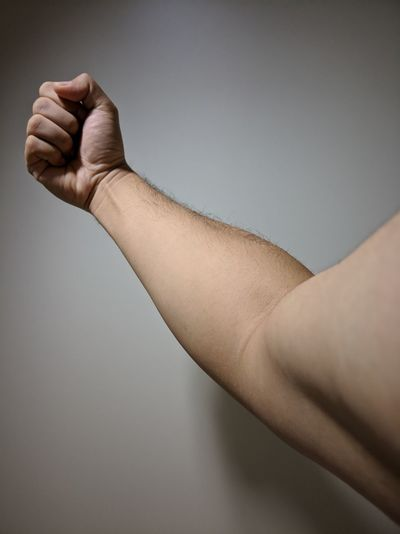 Cropped Hand Of Man Flexing Muscles Against White Wall