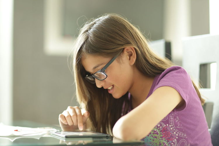Side view of girl using digital tablet at table