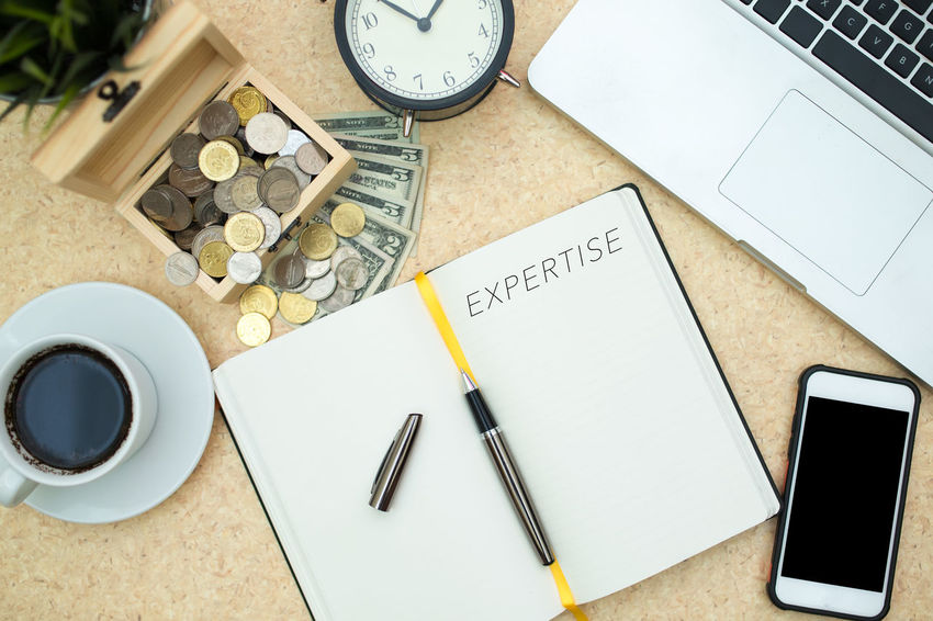 WORD 'EXPERTISE' ON THE NOTE BOOK WITH OFFICE EQUIPMENT Notebook USD Money Clock Laptop Notebook Timetable Project Plan Focus Business Strategy Pen Wireless Technology Portable Information Device High Angle View Diary Indoors  Mobile Phone No People Time Technology Wristwatch Day Close-up