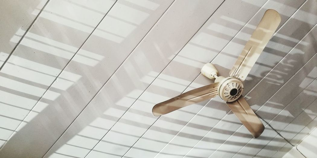 Low angle view of fan hanging from ceiling at home