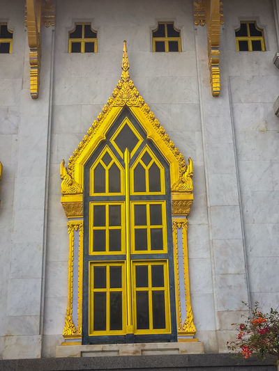 Beautiful golden window with white cement background in Thai temple. Architecture Building Building Exterior Built Structure Closed Day Door Entrance Façade Glass - Material Gold Colored Golden Window History House No People Ornate Outdoors Residential District Temple Wall Temple Walls Temple Window The Past Wall - Building Feature Window Window Frame Window Sill Window View Yellow