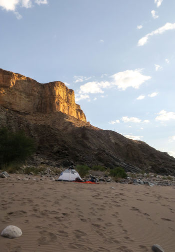 Hiker's campsite setup on sandy terrain under mountain rock face Adventure Beauty In Nature Camping Exploration Explore Hiking Landscape Landscape_Collection Mountain Mountain Range Nature Nature Outdoor Photography Outdoors Peak Rock - Object Sand Tent Tranquil Scene Travel Wilderness