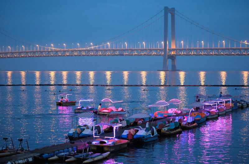 Pedal boats moored on pier against bay bridge at xinghai bay
