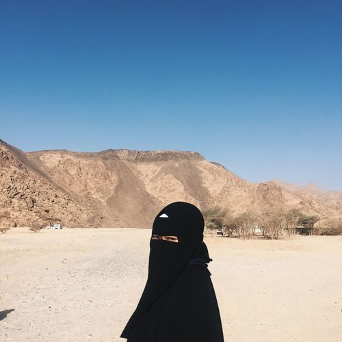 Portrait of woman in hijab standing on arid landscape against clear blue sky