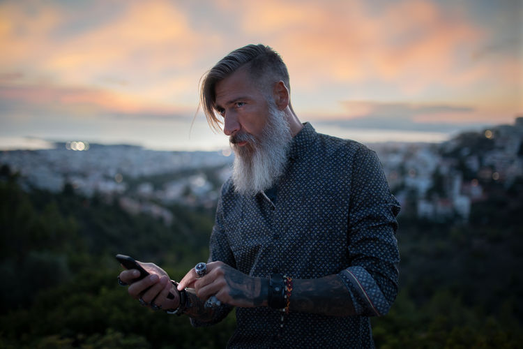Man with beard using phone while standing against sky during sunset