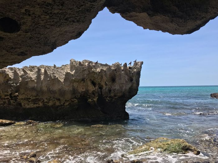 Limestone rocks outside a cave in the ocean. Limestone Rocks Limestone Water Sea Rock Sky Beauty In Nature Scenics - Nature Rock - Object Tranquility Nature Solid Tranquil Scene Horizon Over Water Rock Formation No People Outdoors Idyllic
