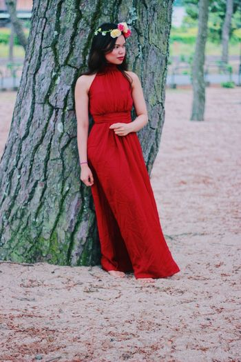 Woman in red dress standing against tree trunk