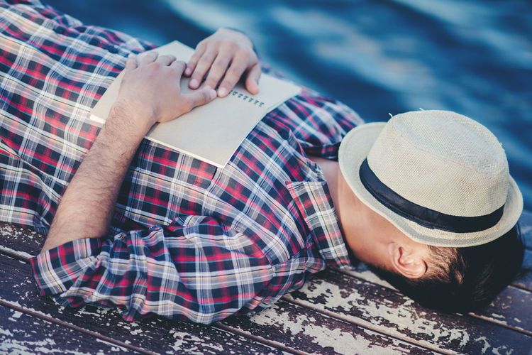 Midsection of man sleeping in hat