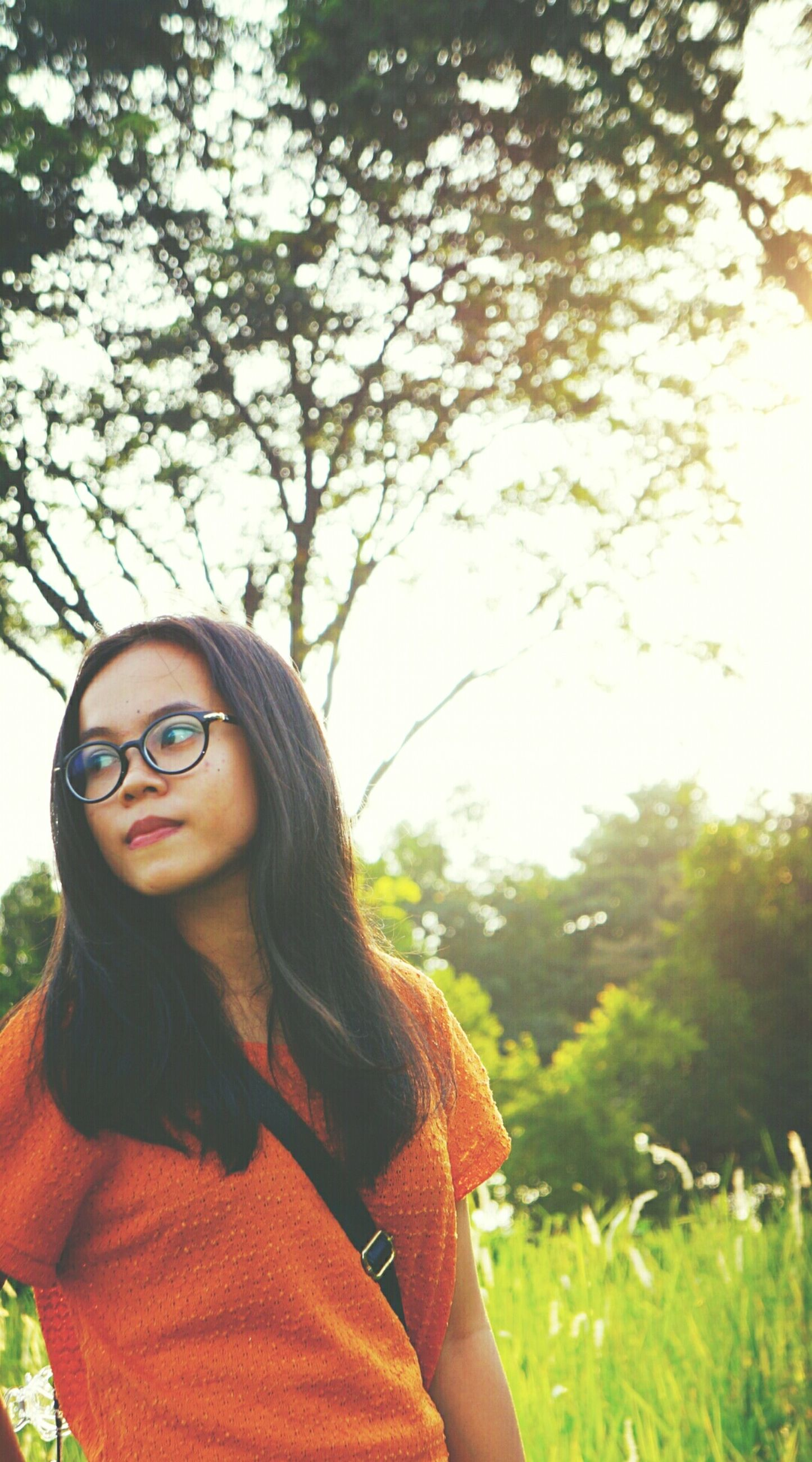 tree, lifestyles, young adult, leisure activity, person, young women, casual clothing, focus on foreground, headshot, front view, smiling, portrait, holding, looking at camera, waist up, sunglasses, day