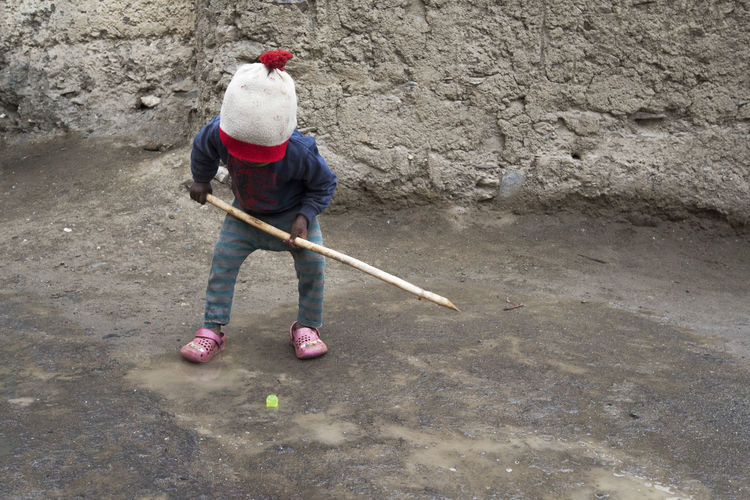 Toddler Playing With Stick Against Concrete Wall