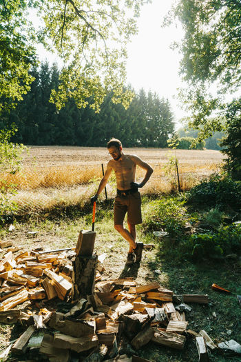 Full length of shirtless lumberjack standing by wood on field