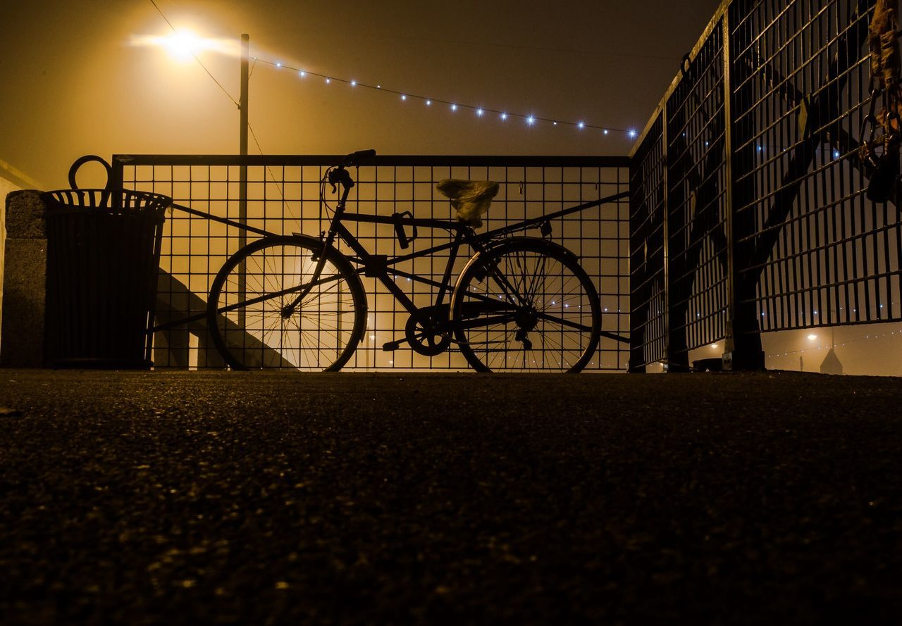 Silhouette bicycle parked against railing and sky at night