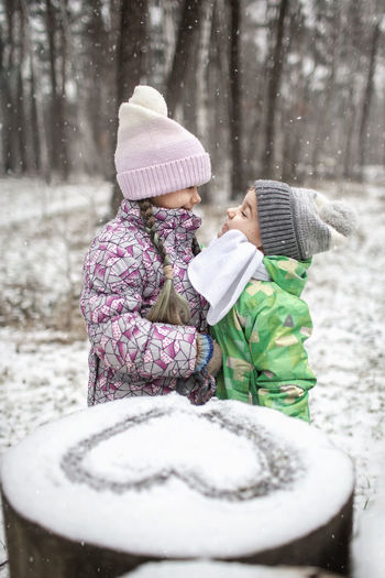 Cute sibling embracing while standing by heart shape on snow outdoors
