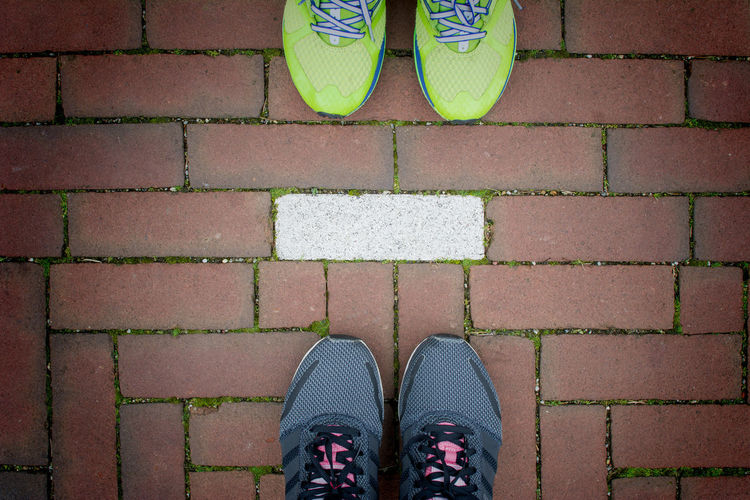 Two pairs of running shoes standing behind each others on red brick walkway with white line separate , Runner couple exercising Couple Exercise Standing Travel Day Flooring Footpath Human Foot Human Leg Lifestyles Paving Stone Red Brick Runner Shoe Two Pairs Walkway White Line