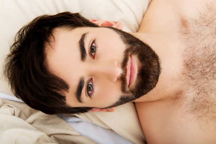 Portrait Of Shirtless Young Man Relaxing On Bed
