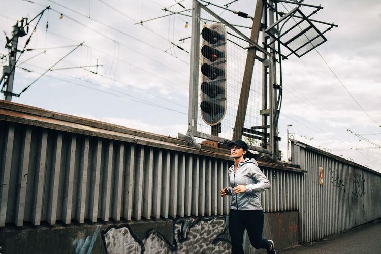 Man standing on bridge against sky in city