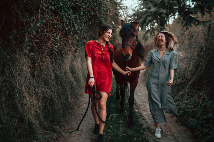 Full length of laughing women walking with horse in forest