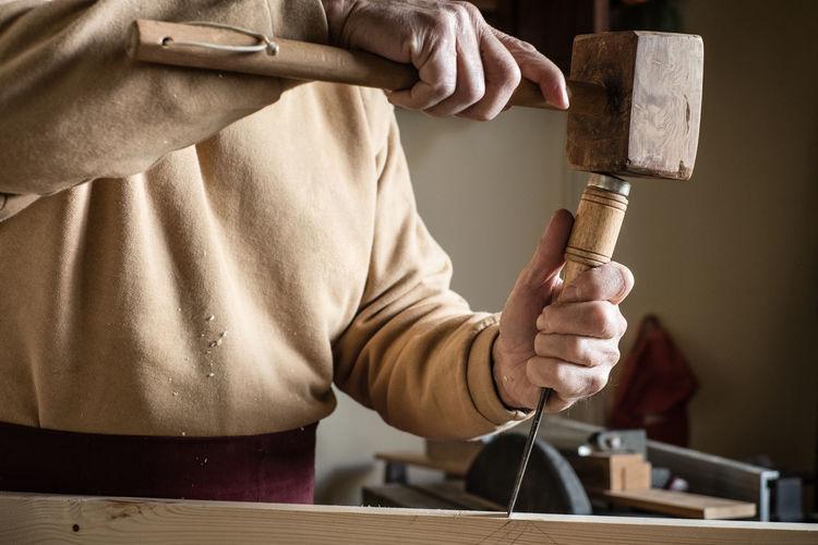 Midsection of carpenter using hammer in workshop