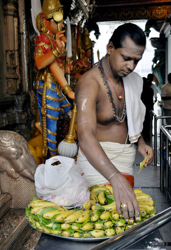 Priest with banana offering in Hindu temple in Singapore. Bananas Bare Chests Beads Beliefs Carvings Hindu Indoors  Lifestyles Offerings Priests Real People Religion Singapore Statues Temples Traditional Dress Vertical