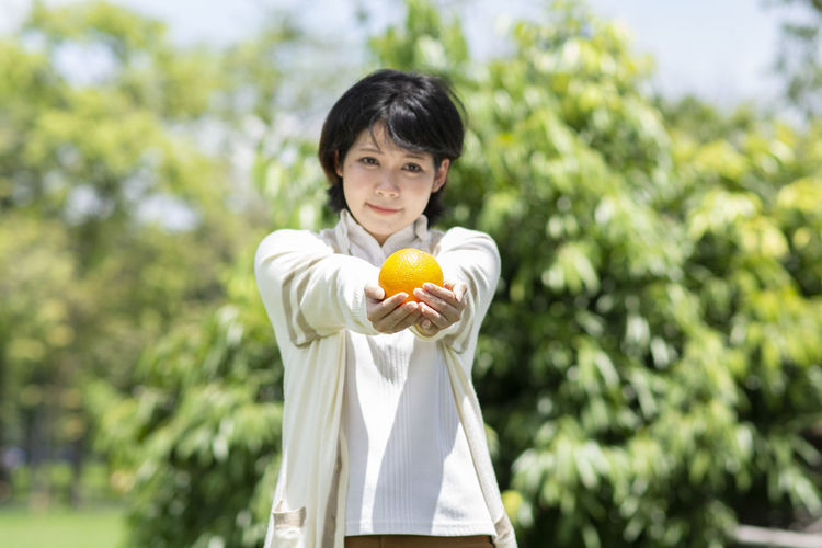 Food Food And Drink Healthy Eating Fruit One Person Wellbeing Holding Healthy Lifestyle Front View Portrait Waist Up Citrus Fruit Looking At Camera Day Casual Clothing Freshness Smiling Young Adult Orange Color Orange - Fruit Orange Outdoors Hairstyle