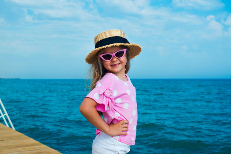 Funny face kid in sunglasses and straw hat posing on sea shore