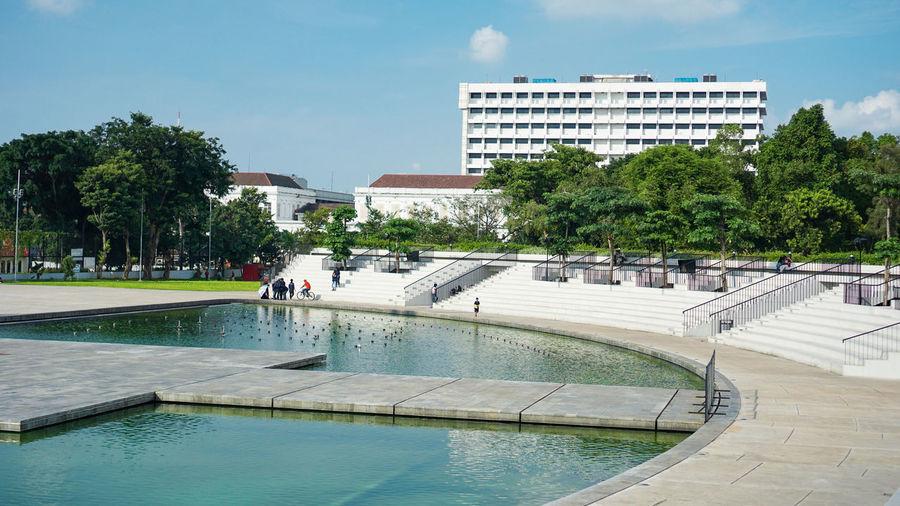 Swimming pool by buildings in city against sky