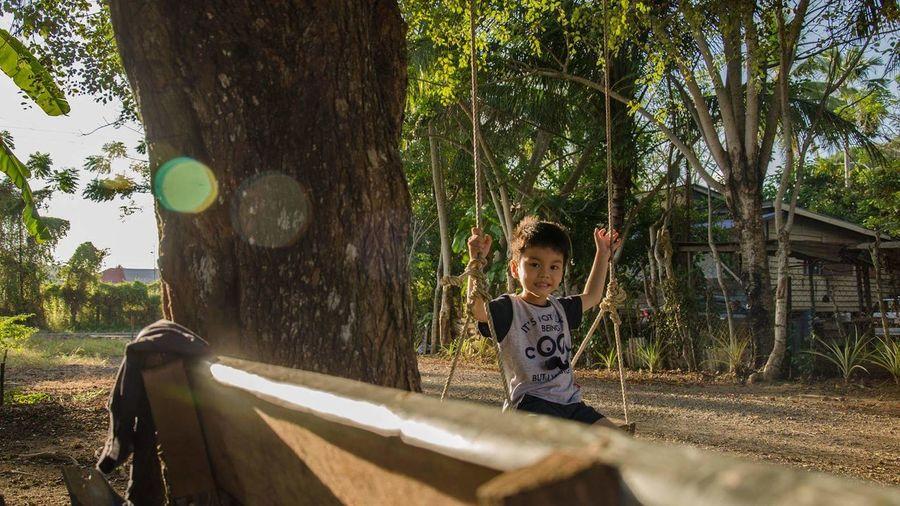 Portrait of boy sitting on swing in playground