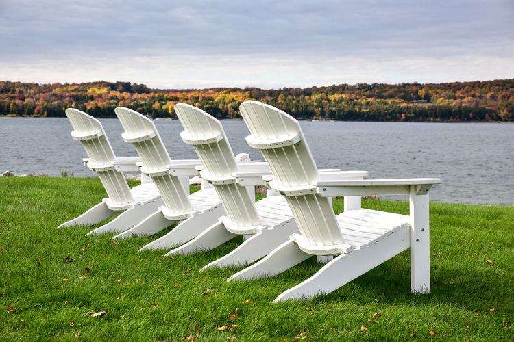 Row of chairs on lakeshore against sky