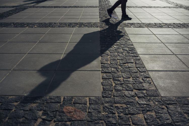 Low section of woman walking on cobblestone street
