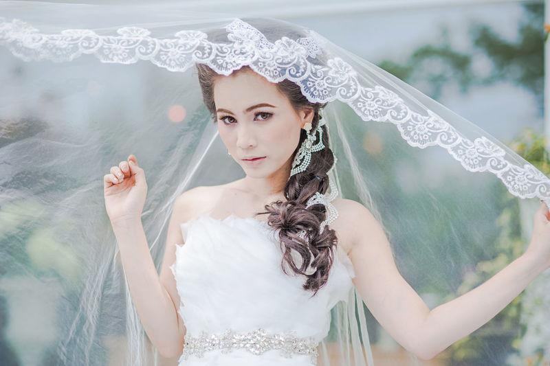 Portrait Of Bride Wearing Wedding Dress Standing At Park