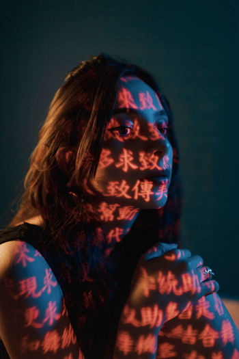 Portrait of woman in illuminated mask