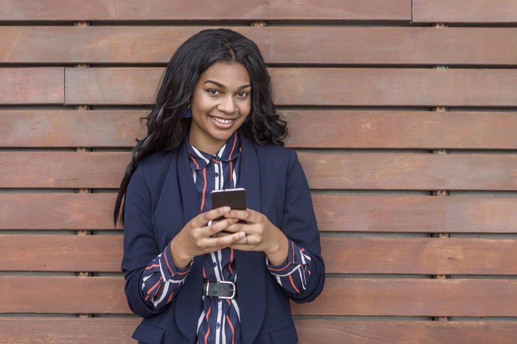 Portrait of smiling young businesswoman using phone while standing wooden planks