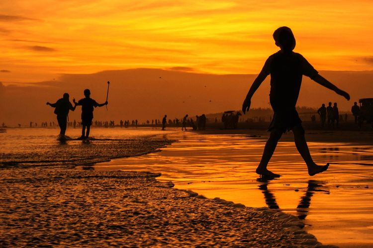 Silhouette Boy Walking At Beach Against Sky During Sunset