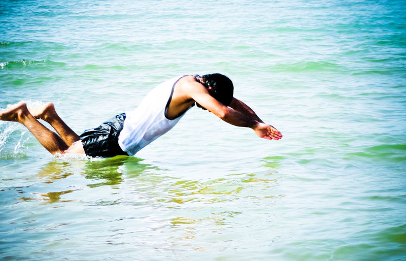 Side View Of Man Jumping In Sea