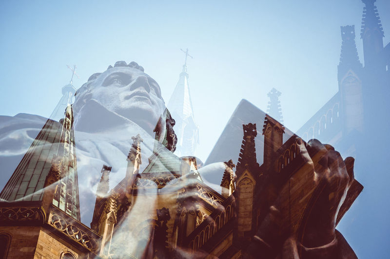 Double exposure of statue and church against sky