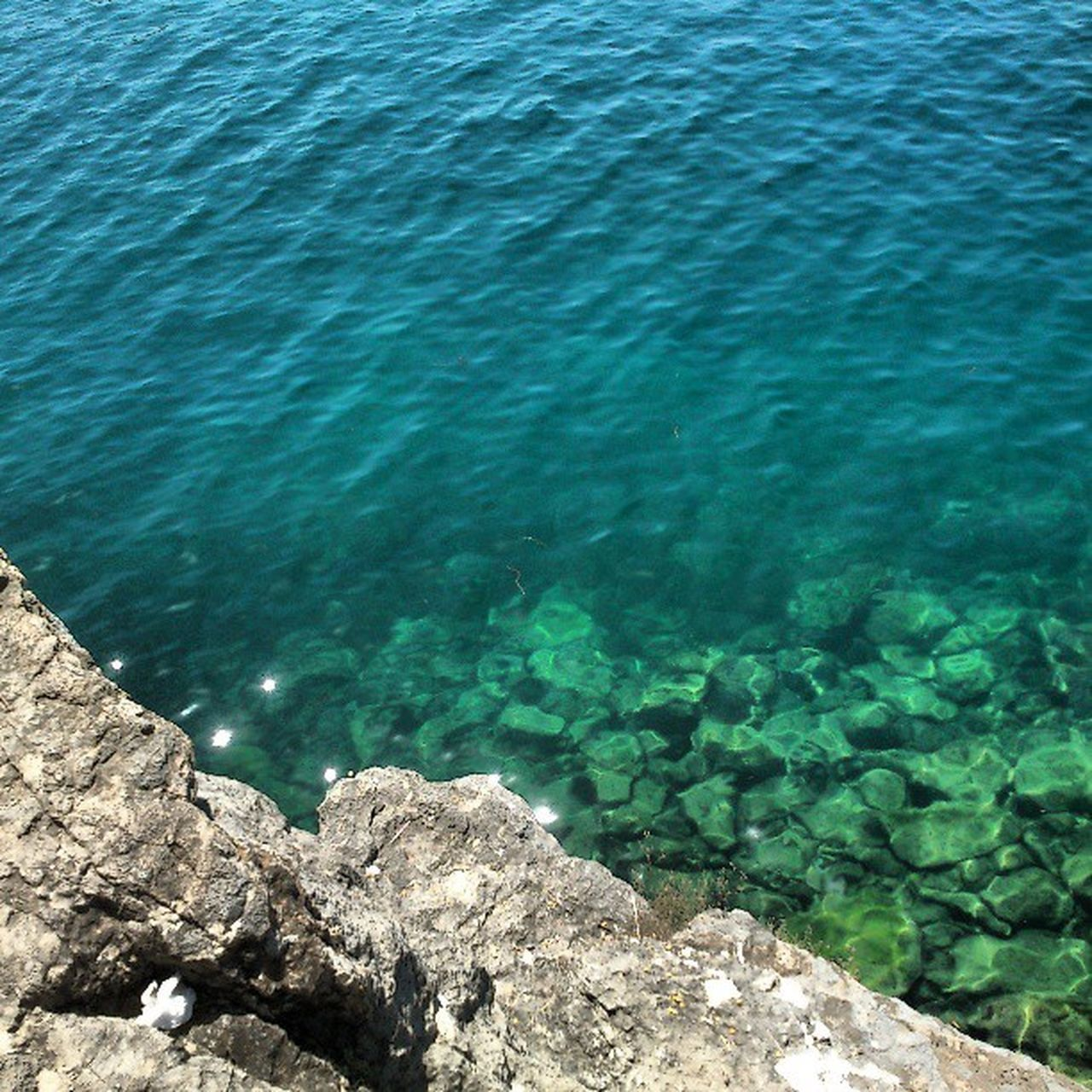 water, sea, high angle view, rock - object, tranquility, beauty in nature, nature, rippled, tranquil scene, blue, scenics, rock, day, rock formation, outdoors, idyllic, no people, sunlight, shore, coastline