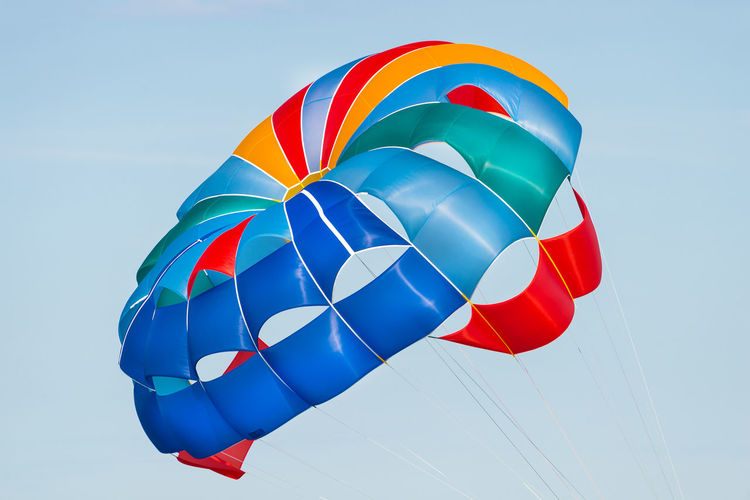 Close up shot of a colorful parachute used for parasailing pulled by a motorboat.