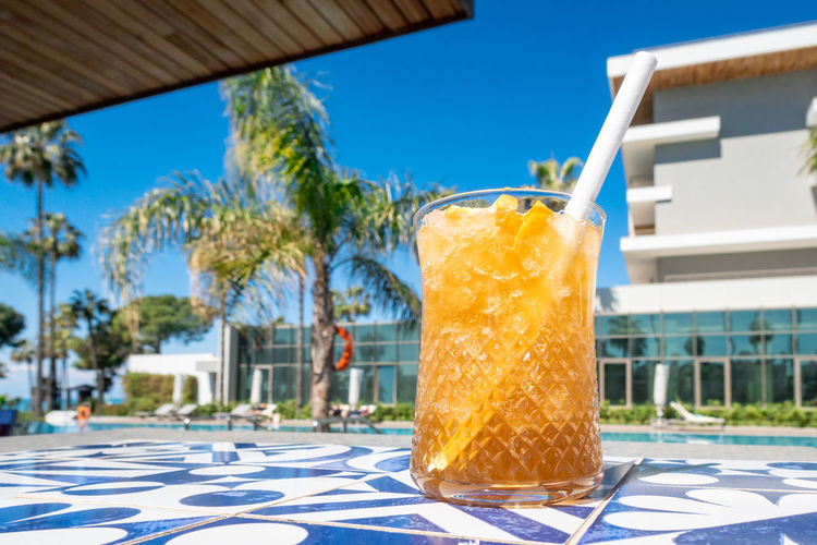View of beer glass at swimming pool against blue sky