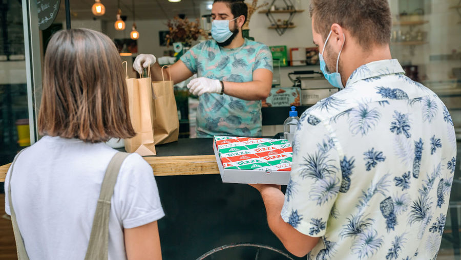 Owner giving pizza take away to customers at restaurant