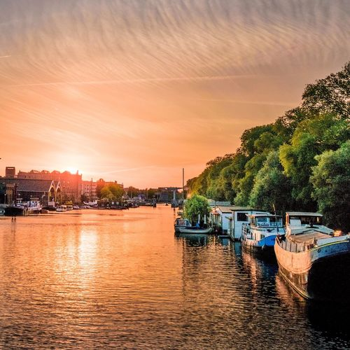 Water Nautical Vessel Transportation Waterfront Boat Tree Mode Of Transport River Reflection Calm Sky Day Orange Color Scenics Tranquility Canal Tranquil Scene Beauty In Nature Sea Cloud - Sky
