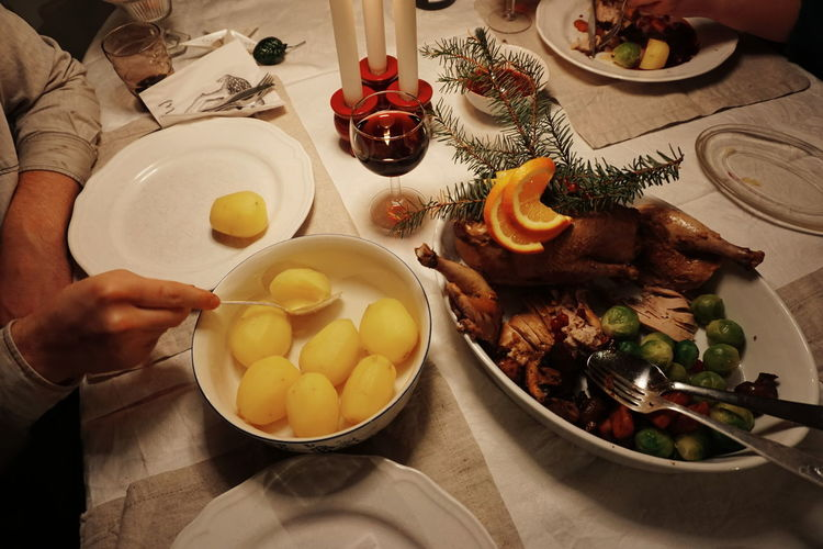Cropped hands having boiled potatoes on table at home