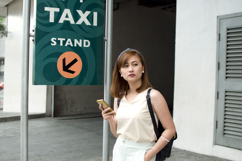 A woman is waiting for a cab using her smart phone Adult Architecture Building Exterior Built Structure City Communication Day Front View Holding Looking At Camera One Person Outdoors People Portrait Real People Road Sign Smiling Standing Waist Up Young Adult Young Women