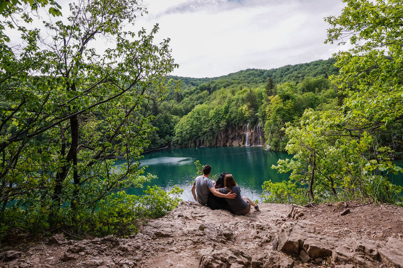 Couple sitting on rock by lake against trees in forest