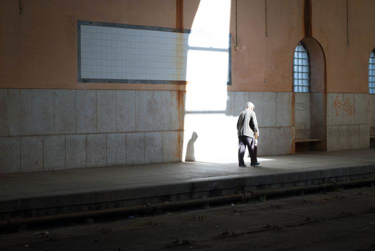 Rear view of men walking in corridor of building