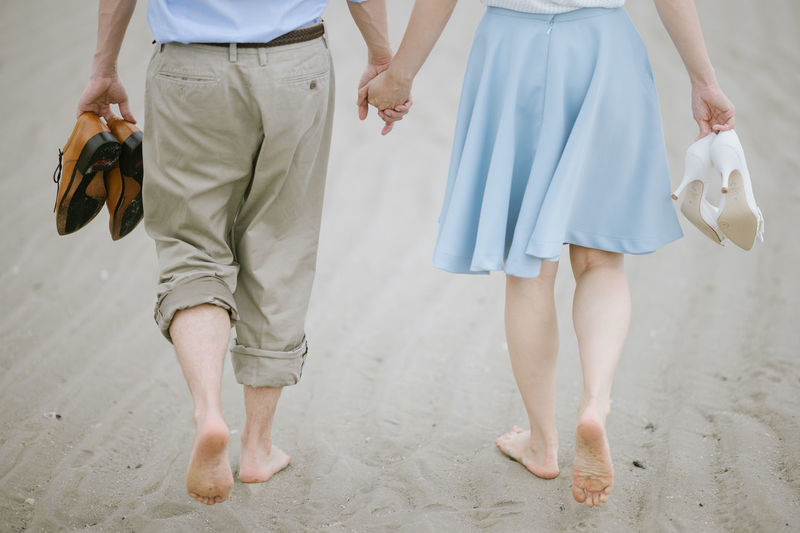 Two People Walking Low Section Women Togetherness Love Positive Emotion Adult Casual Clothing Leisure Activity Bonding Beach Men People Day Couple - Relationship Outdoors Holding Shoes Sand Together Forever Low Angle View Sea Walk On The Beach  Walk Together Shoes