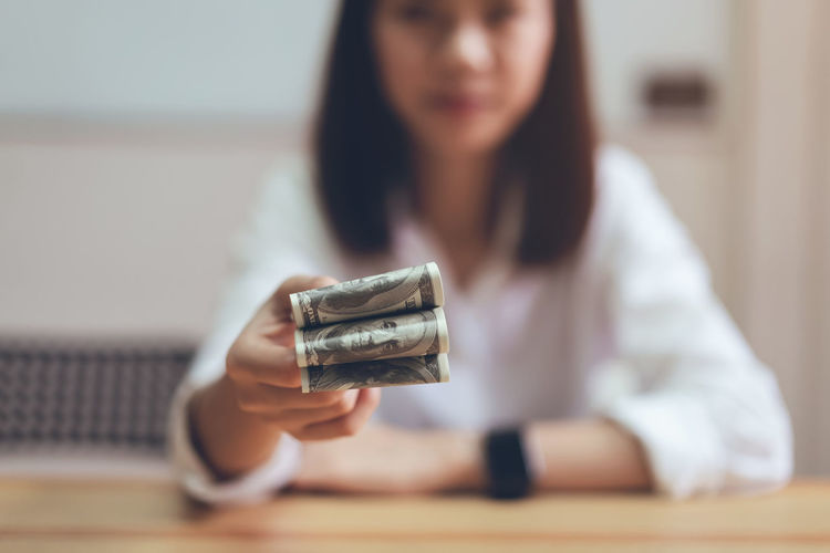 Women holding and give dollar money in the office. The concept of spending by cash. One Person Finance Indoors  Holding Technology Adult Front View Table Hair Focus On Foreground Women Selective Focus Mid Adult Currency Business Paper Currency Lifestyles Real People Headshot Hairstyle